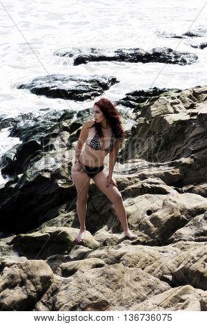 Hispanic Woman Outdoors On Rocks In Bikini With Ocean Water In Background Full-Length