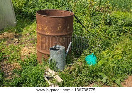 watering pot and barrel of water in the garden.