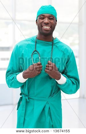joven médico seguro mirando a cámara y sonriendo