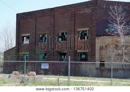JOLIET, ILLINOIS / UNITED STATES - APRIL 26, 2015: A sign on a chain-link fence, topped with barbed wire, tells people not to trespass onto the property of the old Joliet Steelworks in Joliet.