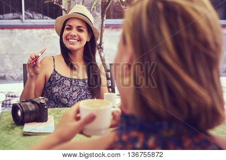 Female friends on holidays young happy women sitting at bar smoking electronic cigarette.