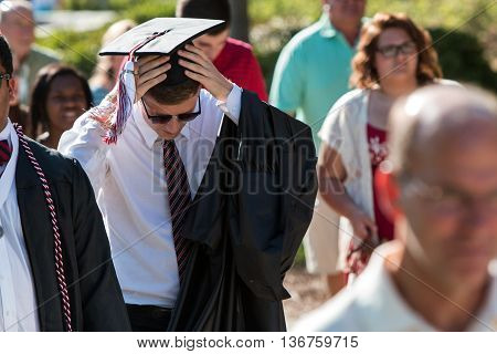 ATHENS, GA - MAY 2016:  A male graduate adjusts his mortarboard and tassle as he walks toward the graduation ceremony at the University of Georgia in Athens GA on May 13 2016.