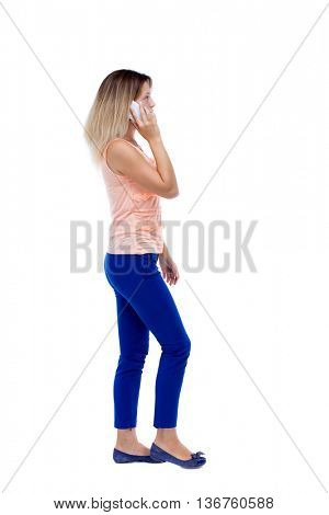 side view of a woman walking with mobile phone. back view ofgirl in motion. backside view of person. Rear view people collection. Isolated over white background. blonde in pink blouse is left on phone