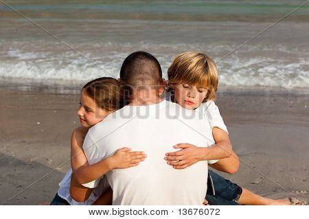 Potrait of Children hugging their father on the beach