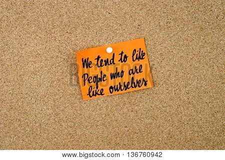 We Tend To Like People Who Are Like Ourselves written on orange paper note note pinned on cork board with white thumbtack copy space available poster