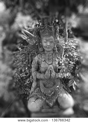 Close up of Grey Buddha statue in flower garden