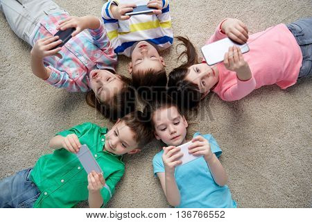 childhood, fashion, friendship and people concept - group of happy smiling little children with smartphones lying on floor