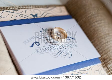 Wedding rings sat upon a wedding invitation