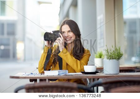travel, tourism, photography, leisure and people concept - happy young tourist woman or teenage girl photographing with digital camera photographing and drinking cocoa at city street cafe terrace