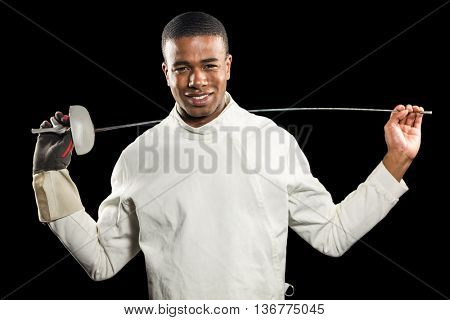 Portrait of swordsman standing with sword on black background