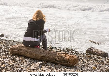 Girl Sitting On The Log On The Coast And Looks At Sea