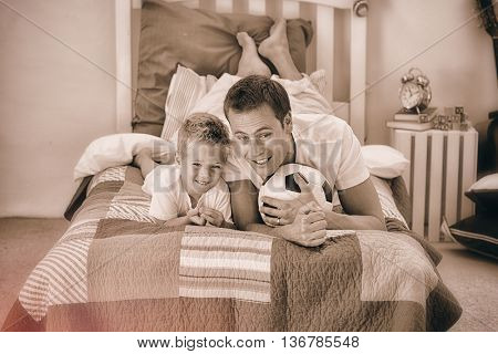 Smiling little boy and his father watching a football match in the kids bedroom