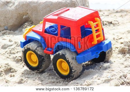 toy plastic car all-terrain vehicle in sand