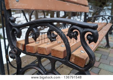 Forged iron armrest in black on a wooden bench