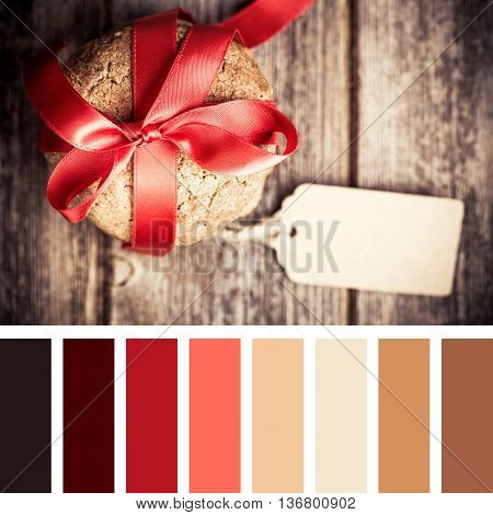 Cookie gift with tag over old wood background. In a colour palette with complimentary colour swatches