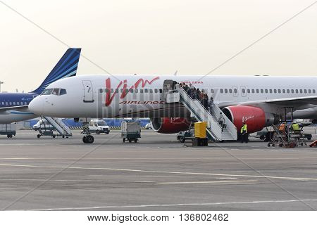 MOSCOW, RUSSIA - SEPTEMBER 26, 2014: Passengers climb the ladder into the plane Boeing 757 Vim airlines