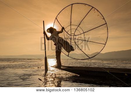 INLE LAKE MYANMAR - JANUARY 14 2016: Unidentified Burmese fisherman on bamboo boat catching fish in traditional way with handmade net. Inle lake Myanmar Burma
