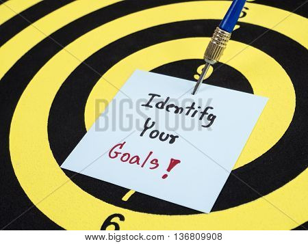 Close up of handwriting Identify your goal on notepaper with arrow and dart board. (Selective focus)