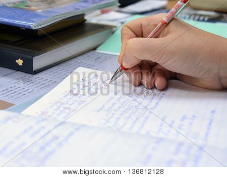The teacher checks the notebook with the task of evaluating and exposes