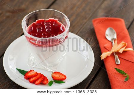 Panna cotta with strawberry syrop served on brown wood closeup. Glass with panna cotta dessert and strawberry slices on white saucer and teaspoon on orange napkin on wooden background