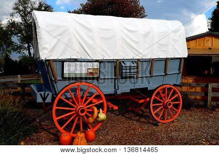 Intercourse Pennsylvania - October 13 2015: A Pennsylvania conestoga covered wagon with autumn pumpkins and gourds at Kitchen Kettle Village *