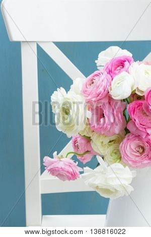 Pink and white ranunculus flowers bouquet in vase on chair close up