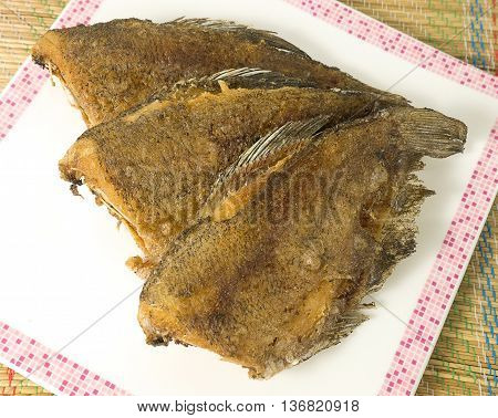Asian Food and Cuisine Oriental Food Deep Fried Gourami Fish or Snakesskin Fish on A White Plate.