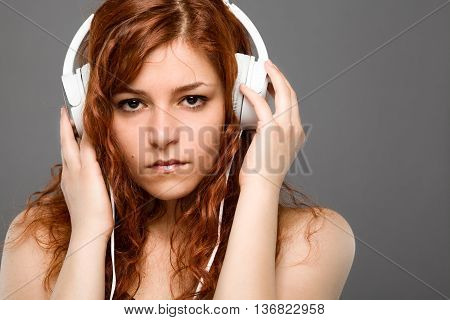 Redhead Woman Listening to Music with Headphones
