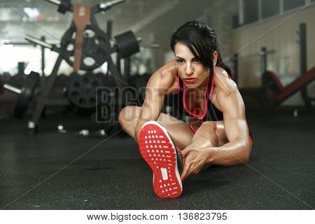 Photo Girl Sitting On The Floor. Girl Doing Stretching With A Serious Expression On His Face