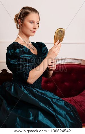 portrait victorian woman with mirror sitting on fainting couch
