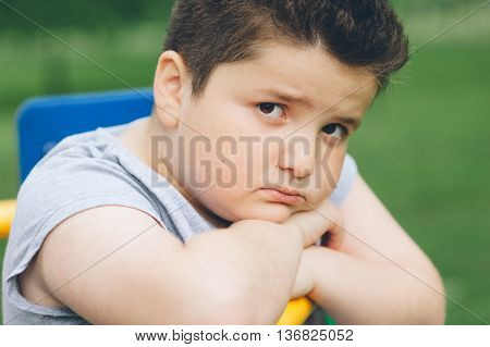 sad fat boy sitting on sports simulator