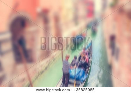 Defocused Background with Gondola full of People enjoying a cruise with a gondolier in a narrow water canal between old buildings in Venice Italy.