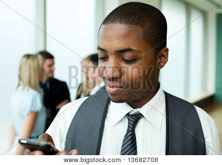 Afro-americano uomo d'affari, l'invio di un testo in ufficio