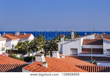 Roofs from terracotta tiles palm trees blue sea. Travel destination. Costa Dorada Spain. Horizontal.