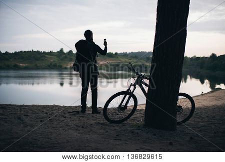 Backpacker With Parked Mtb Against Tree Taking Pictures Of Dune Lake