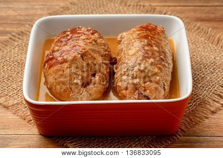 Roasted meat roulades with sauce on wooden background.
