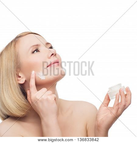 Beautiful middle aged woman with smooth skin and short blond hair applying moisturizing cream on face. Beauty shot. Isolated over white background. Copy space. poster
