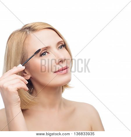 Beautiful middle aged woman with smooth skin and short blond hair applying fix gel to eyebrows. Beauty shot. Isolated over white background. Copy space. poster