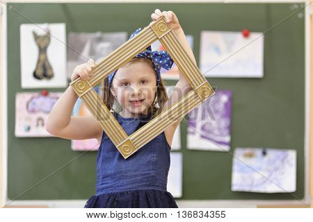 girl looking through decorative frame on background of pictures hung on blackboard in classroom, looking at camera, turned frame diagonally
