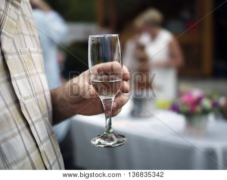 Male hand holding a glass of wine or champagne a party on the blurred background. Outdoor shot concept of special occasion celebrating