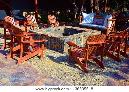 Modern wooden chairs surrounding a courtyard fire pit creating a rustic atmosphere in a residential garden