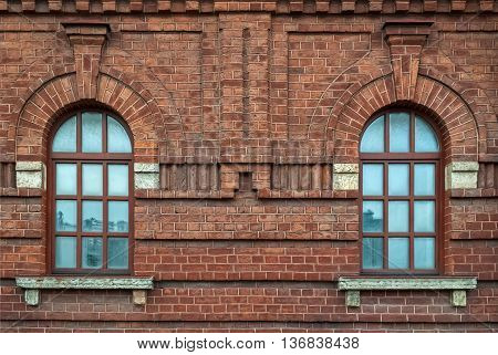 Two windows with an arch on the background wall of brown brick. From the series window of Saint-Petersburg.
