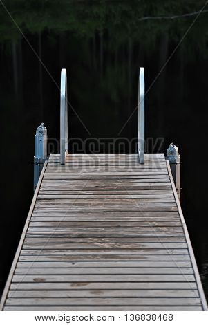 Small bridge for bathing in a forest lake a cool summer evening.