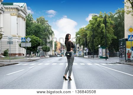 Lonely woman with a bag over his shoulder at the empty road on the street goes away