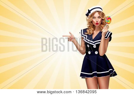 Surprised pin-up sailor girl with a lollipop pointing aside on cartoon style background.