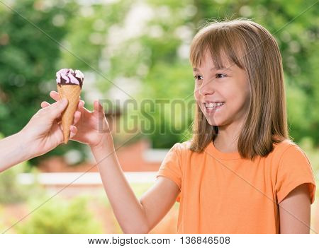 Woman hand holding an ice cream cone and smiling cute girl outdoors in park