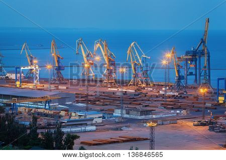Sea commercial port at night in Mariupol Ukraine. Industrial view. Cargo freight ship with working cranes bridge in sea port at twilight. Cargo port logistic