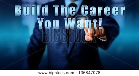 Human resources manager is pressing the phrase Build The Career You Want! on a virtual screen. Motivational business metaphor. Recruitment and talent acquisition concept. Torso of man in blue suit. poster