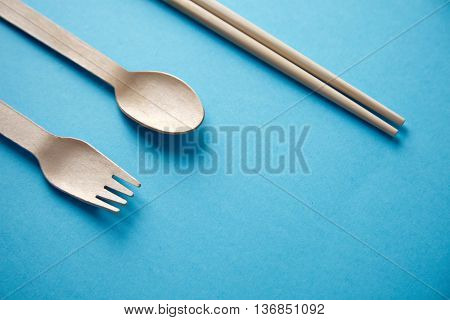Various kitchen utencils for takeaway: asian chopsticks, spoon or fork made from recycled paper or wood, eco friendly, top view isolated on blue mockup