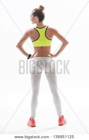 Full length portrait of pretty sporty girl standing and posing with arms akimbo. She is smiling. Focus on her fit back. Isolated